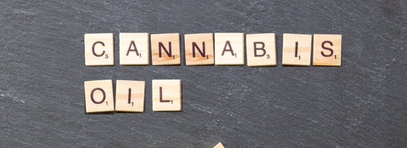 cannabis oil spelled by wooden tiles